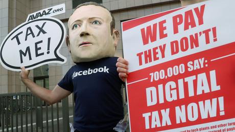 Un manifestant portant un masque à l'effigie du PDG de Facebook, Mark Zuckerberg, appelle à taxer les géants du numérique à la veille d'une réunion des ministres des Finances de l'Union européenne, devant le siège de l'UE à Bruxelles, le 4 décembre 2018 (illustration).