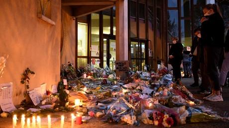 A l'entrée du collège de Conflans-Sainte-Honorine, le 17 octobre, des dizaines de fleurs et de bougies rendent hommage au professeur tué par un islamiste.