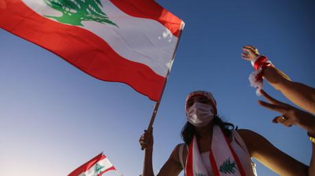 Une manifestante libanaise lève un drapeau national lors d'une manifestation marquant le premier anniversaire du début d'un mouvement de protestation antigouvernementale à l'échelle nationale, dans la capitale Beyrouth le 17 octobre 2020 (image d'illustration).