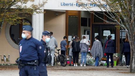 Des gens déposent des fleurs devant le collège du Bois d'Aulne, où enseignait Samuel Paty, le 17 octobre 2020.
