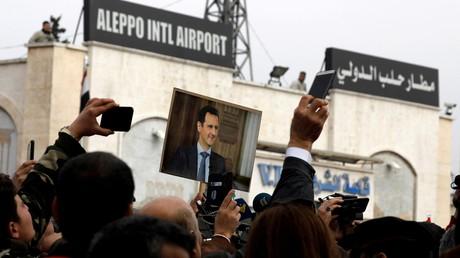 Des gens brandissent une photo du président syrien Bachar al-Assad à l'aéroport d'Alep, février 2020 (image d'illustration).