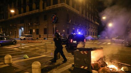 Un policier anti-émeute italien passe devant une poubelle en feu dans le centre ville de Naples, le 23 octobre 2020.