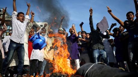 Des musulmans brûlent une effigie du président français Emmanuel Macron lors d'une manifestation appelant au boycott des produits français et dénonçant Macron pour ses commentaires sur les caricatures du prophète Mahomet, à Dacca, Bangladesh, le 30 octobre 2020.