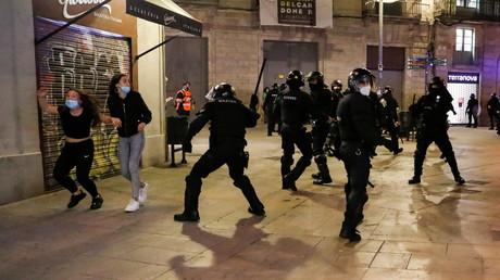 Des manifestants courent pour échapper à la police lors de la manifestation contre les restrictions de circulation à Barcelone, le 30 octobre 2020.