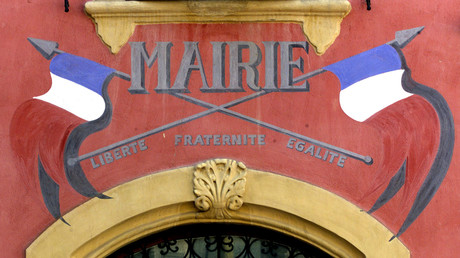 La devise de la République française et des drapeaux tricolores peints sur la façade de l'hôtel de ville de Carla-Bayle, un village du sud-ouest de la France (image d'illustration).