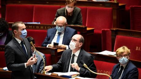 Le ministre français de l'Action et des Comptes publics Olivier Dussopt (debout) lors d'une session de questions au gouvernement à l'Assemblée nationale française à Paris le 13 octobre 2020 illustration).