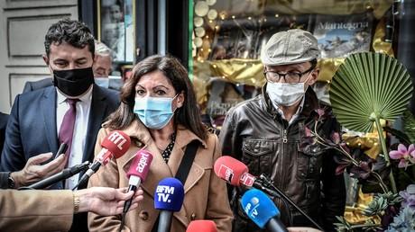 La maire de Paris Anne Hidalgo (C) parle à la presse avec Sylvain Tesson (R) devant la Librairie des Abbesses dans le quartier de Montmartre, à Paris, pour le lancement de l'opération «Rallumez les feux de nos librairies » le 2 novembre 2020.