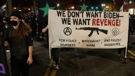 Des manifestants munis d'une banderole portant le slogan  «On ne veut pas de Biden, on veut la vengeance -  Pour les meurtres commis par la police, les guerres impérialistes, et les massacres fascistes», à Portland, dans l'Oregon, le 4 novembre 2020.