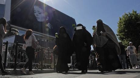 Trois femmes en voile intégral, dont l'une montre un chèque symbolisant l'amende qu'elle risque de payer en raison de la loi interdisant le port du voile intégral dans l'espace public en France ; photographie prise à Cannes en mai 2011 durant le festival (image d'illustration).