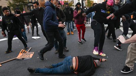 Un militant pro-Trump gisant sur le sol est frappé par des manifestants anti-Trump au Black Lives Matter Plaza à WashingtonDC, le 14novembre 2020.