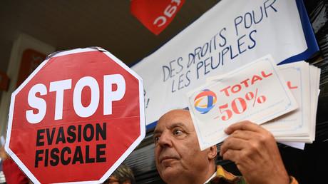 Un activiste de l'ONG Attac (Association pour la taxation des transactions financières et pour l'action citoyenne) brandit un panneau «Stop à l'évasion fiscale» durant une manifestation à Marseille, le 12octobre 2019 (image d'illustration).