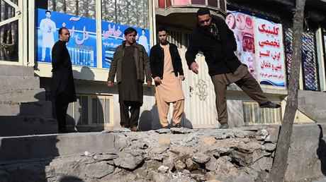 Des hommes observent les dommages causés par des tirs de roquettes à Kaboul le 21 novembre 2020