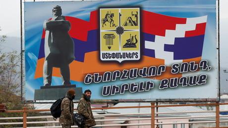 Deux hommes en treillis marchent devant un panneau représentant le drapeau du Haut-Karabagh dans sa capitale, Stepanakert, le 16 novembre 2020 (image d'illustration).