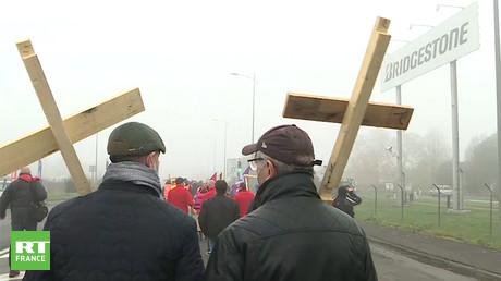 Des salariés de l'usine Bridgestone portent des croix en bois sur lesquelles ils ont inscrit leurs matricules