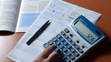 Une personne utilise une calculatrice pour remplir sa déclaration d'impôt sur le revenu, le 31 mars 2013 (image d'illustration).