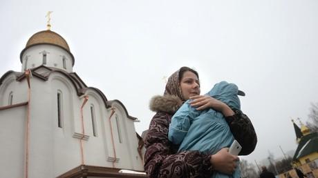 Une femme avec un enfant devant une église à Moscou