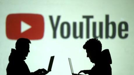 Des utilisateurs d'ordinateur portable devant le logo de YouTube, le 28 mars 2018 (image d'illustration)
