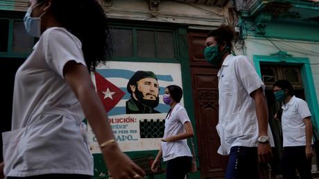 Des étudiants en médecine passent devant une image du défunt président cubain Fidel Castro, dans le centre de La Havane, Cuba, le 12 mai 2020. (Image d'illustration)