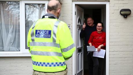 Un volontaire de la police propose à des résidents de se faire tester, au Royaume-Uni.