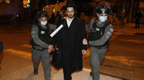 Les forces de sécurité israéliennes arrêtent un juif ultra-orthodoxe lors d'une manifestation contre les restrictions, à Jérusalem le 9 février 2021.