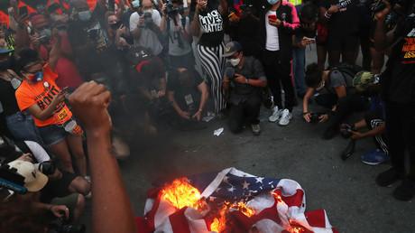 Des manifestants rassemblés à l'appel de Black Lives Matter brûlent un drapeau américain à Washington DC, le 4 juillet 2020.
