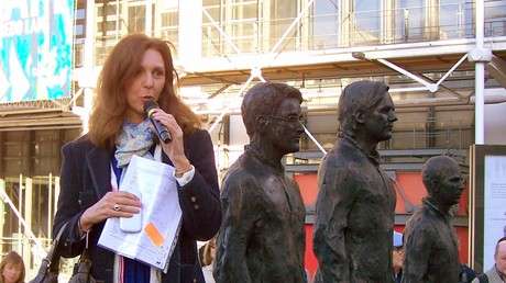 La lanceuse d'alerte Stéphanie Gibaud devant les statues d'Edward Snowden, Julian Assange et Chelsea Manning, près du centre Pompidou à Paris, en septembre 2015.