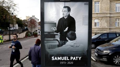 Des piétons passent devant une affiche représentant le professeur de français Samuel Paty à Conflans-Sainte-Honorine, le 3 novembre 2020,
