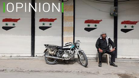 Un homme assis devant un magasin fermé, affichant le drapeau syrien, le 10 mars 2021 à Douma (illustration).