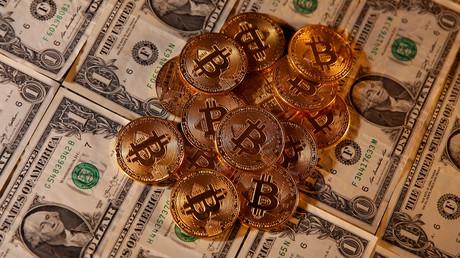 Des dollars et des bitcoins présents sur une même image le 27 janvier 2020.