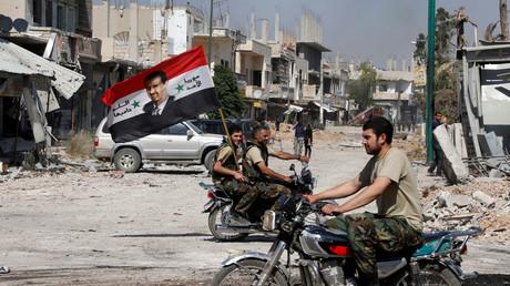 Des membres des forces de l'ordre fidèles au président Bachar el-Assad défilent avec un drapeau à Qusair en Syrie le 5 juin 2013 (image d'illustration).