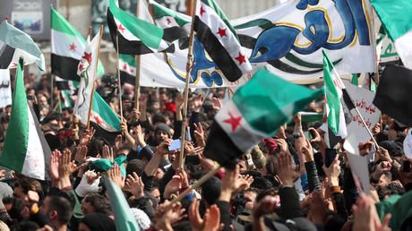 Des manifestants agitent des drapeaux de l'opposition syrienne lors d'une manifestation dans la ville syrienne d'Idlib, tenue par les rebelles, le 15 mars 2021.