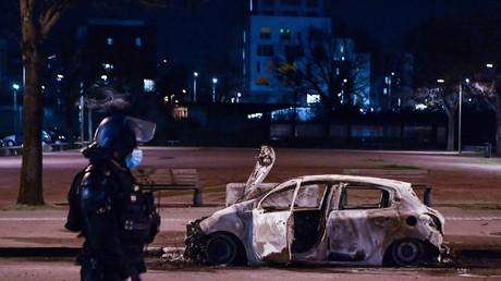 10 mars 2021 à Bron, en banlieue de Lyon, un membre des forces de sécurité intérieure devant un véhicule carbonisé, après des violences urbaines qui ont duré trois nuits (image d'illustration).
