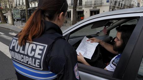 L'attestation de déplacement dérogatoire d'un automobiliste est contrôlée par une policière à Tours (Indre-et-Loire) lors du premier confinement, le 17mars 2020 (image d'illustration).