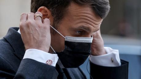 Le président français Emmanuel Macron enfile son masque à l'Elysee le 23 mars 2021.