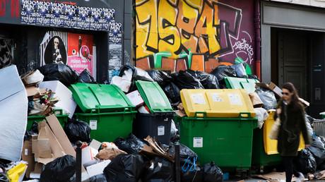 Une femme passe devant des ordures empilées sur le trottoir à Paris le 7 février 2020 (image d'illustration).