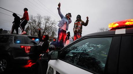 Brooklyn Center, Minnesota, aux Etats-Unis, des individus sautent sur des voitures de police le 11 avril 2021 après un fait divers dans lequel un homme recherché par la police a été tué après avoir refusé de se soumettre à un contrôle.