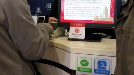 Le symbole du yuan numérique chinois, ou e-CNY, est visible au-dessus de ceux des applications de paiement dématérialisé Wechat Pay et Alipay à un comptoir d'un centre commercial de Pékin, le 10 février 2021 (illustration).