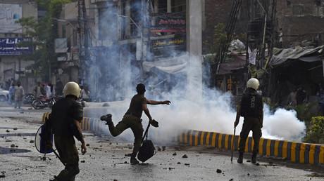 Un policier jette une pierre en direction des partisans de Tehreek-e-Labbaik Pakistan (TLP) lors d'une manifestation à Lahore le 12 avril 2021, après l'arrestation de leur chef, qui a appelé à l'expulsion de l'ambassadeur de France.