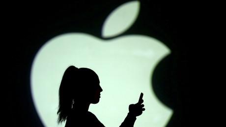 Une silhouette féminine tient son smartphone devant un logo d'Apple le 28 mars 2018 (image d'illustration).