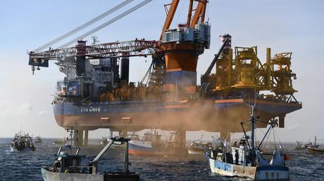Des bateaux de pêche encerclent le navire plateforme de forage Aeolus dans la baie de Saint-Brieuc, dans l'ouest de la France le 7 mai 2021, pour protester contre le projet de construction de 62 éoliennes au large de la baie.