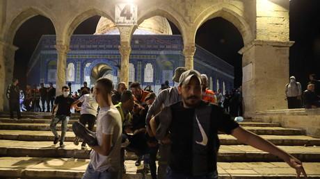 Un Palestinien blessé est évacué après des affrontements avec la police israélienne dans l'enceinte qui abrite la mosquée al-Aqsa, à Jérusalem, le 7 mai 2021.
