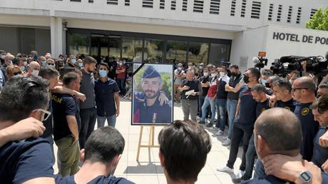 Des policiers se rassemblent autour d'un portrait de leur collègue  Eric Masson assassiné le 5 mai, devant le commissariat principal d'Avignon, dans le sud de la France, le 9 mai 2021.