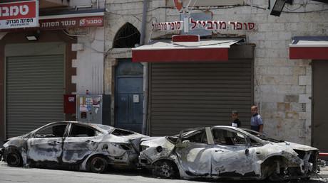 Des véhicules brûlés lors d'une nuit de tensions à Lod, le 11 mai 2021.