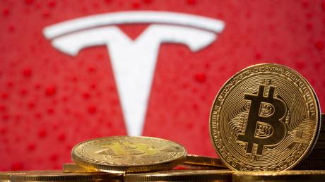 Des pièces frappées du logo Bitcoin, devant le logo de Tesla, à Zenica, le 9 février 2021 (image d'illustration)