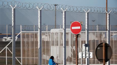 Un migrant assis devant la clôture entourant le port de Calais, le 21 février 2019 (image d'illustration)
