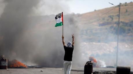 Un manifestant tenant un drapeau palestinien à Naplouse, en Cisjordanie, le 14 mai 2021.