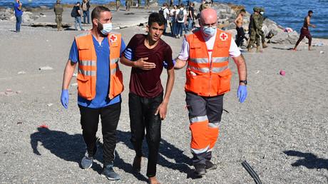 Des membres de la Croix rouge espagnole aident un migrant qui vient tout juste d'arriver à Ceuta après une traversée à la nage le 18 mai 2021 (image d'illustration).