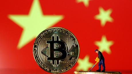 Saynète réalisée avec une figurine de «mineur» sur fond de bitcoins et de drapeau chinois le  9 avril 2019 (illustration).