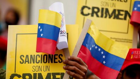 Des partisans du président vénézuélien Nicolas Maduro tiennent des pancartes indiquant