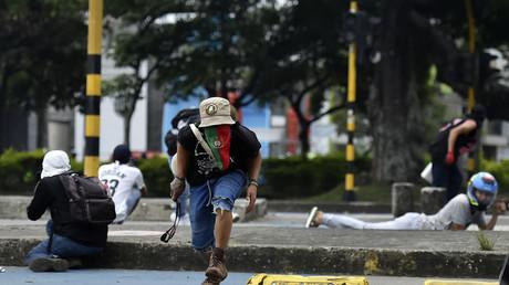 Des manifestants cherchent à s'abriter lors d'affrontements avec la police dans le cadre d'une nouvelle manifestation contre le gouvernement du président colombien Ivan Duque, à Cali, le 28 mai.